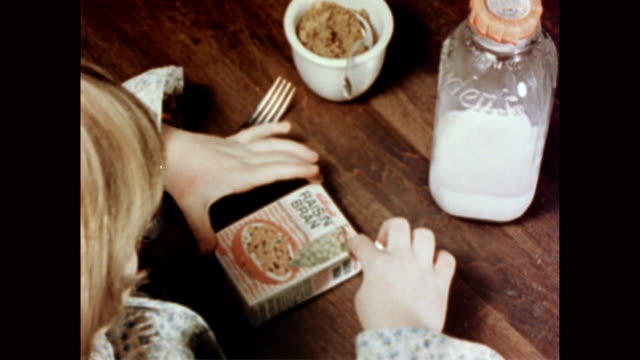 Blonde girl sitting at table with individual serving size cereal box / girl opens the box of Kellogg's Raisin Bran by tearing down the center of the...