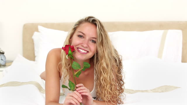Blonde haired woman smelling a rose