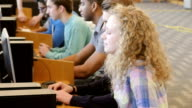 Blonde high school girl walks into frame and sits at computer desk in library