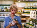 1962 blonde woman looking at canned food in grocery store / industrial