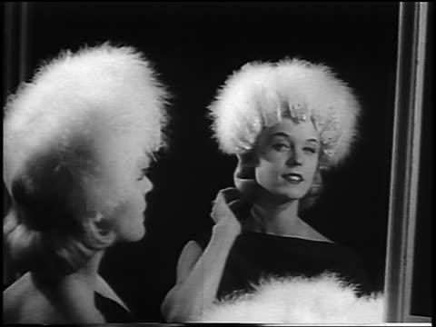 B/W 1956 blonde woman looking in mirror modelling furry hat / newsreel