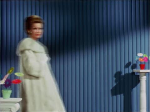 1968 blonde woman modeling white fur coat / industrial