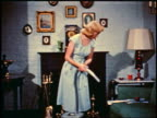 1950 blonde woman picking up metal tube vacuum attachment from sofa