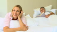 Blonde woman posing on a bed while husband reads a book / Cape Town, Western Cape, South Africa