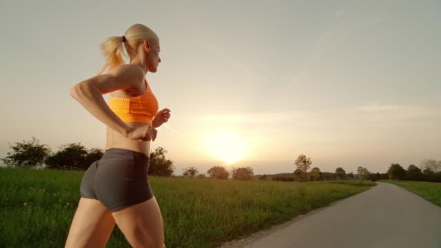 SLO MO TS Blonde vrouw uitgevoerd bij zonsondergang