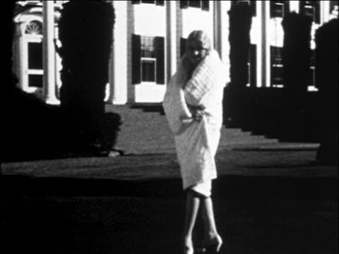 B/W 1929 blonde woman turning + modeling white fur cape outdoors / newsreel