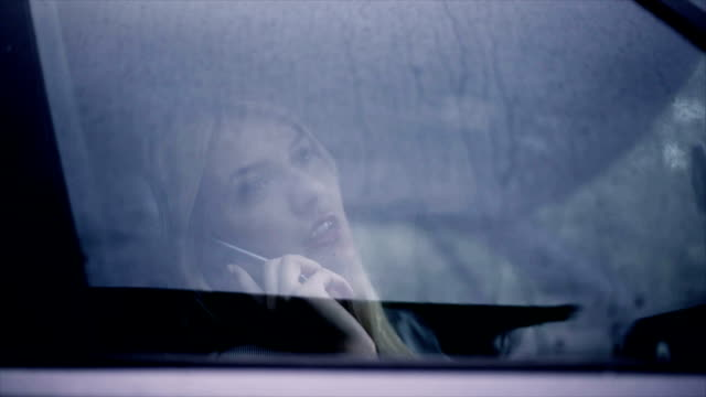 Blonde woman using phone in the car
