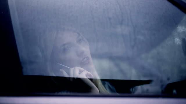 Blonde Frau mit Handy im Auto