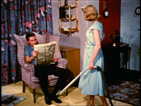 1950 blonde woman vacuuming newspaper from husband sitting in chair + leading him offscreen