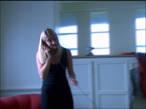 Blonde woman wearing black dress talking on telephone + sitting down in chair