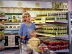 1962 blonde woman with baby in shopping cart walking past shelves of canned food / industrial