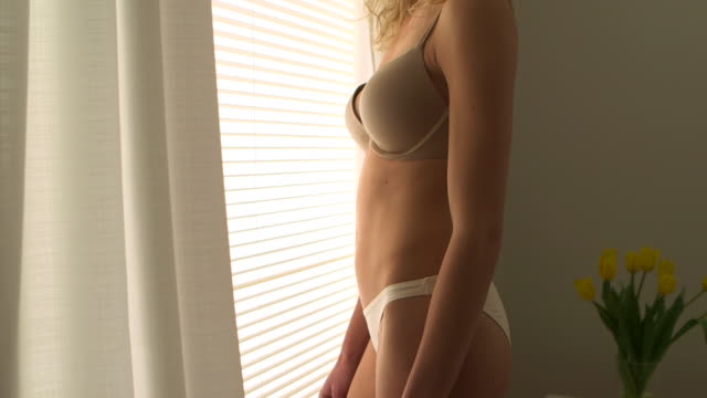 Blonde woman with curly hair standing by window in lingerie