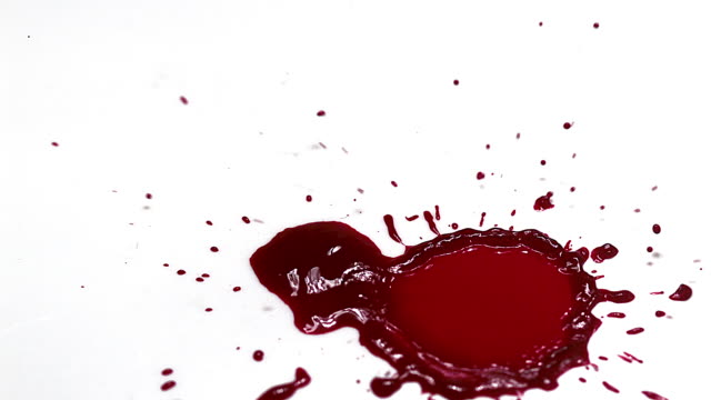 Blood droplets falling against white background, Slow motion