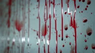 Blood splatters on a white wall and drips