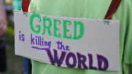 An activist standing at the Monroe County Courthouse wears a sign reading 'Greed is Killing the World' during the Medicare For All March and rally in...