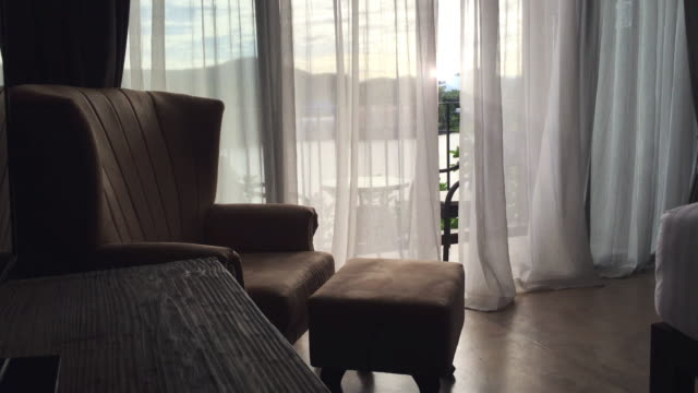 Blowing curtain with a armchair.