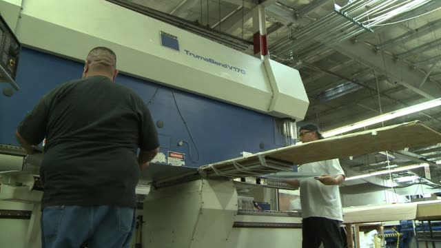 Blue collar work men making manufacturing a variety of flooring products at Arizona Tile presses and punches rollers and medium size machinery