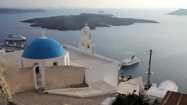 Blue Domed white washed churches of Thira overlooking the Aegean Sea and ferry on the Island of Santorini, Greece, Europe