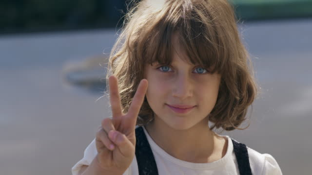 Blue eyed girl gives peace sign and smiles at camera.