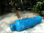 MS blue gas cylinder lying in flood water on beach, tsunami aftermath, Thailand