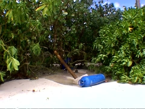 MS blue gas cylinder lying on sand, tsunami aftermath, Thailand