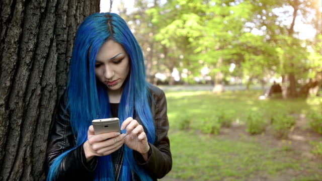Blue haired girl using smartphone