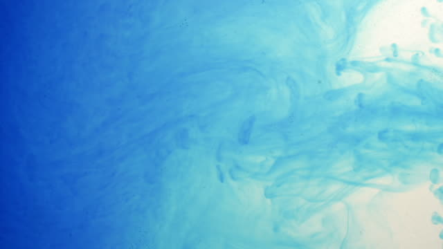 Blue ink squirting and dispersing in a turbulent pattern of swirls