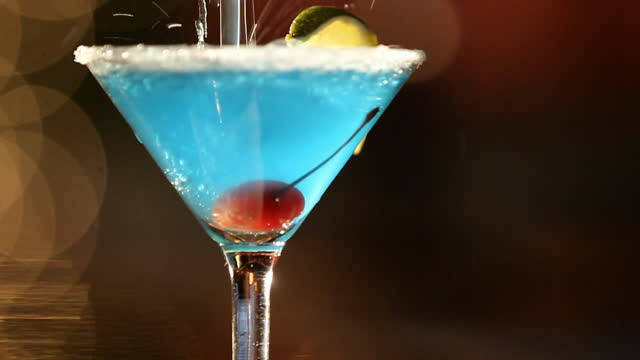 A blue martini pours into a glass.