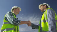 LA  blue sky, no horizon, young and mature construction worker shaking hands