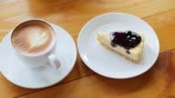Blaubeer-Käsekuchen mit Latte Art Kaffee auf Holztisch für Entspannungs-Konzept, Dolly Schuss