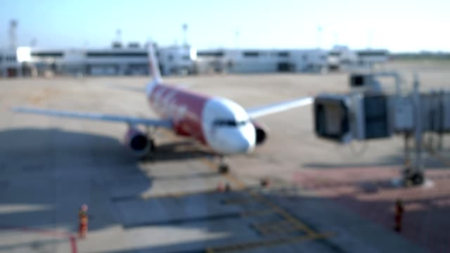 Blurred background airplane moving to connect with boarding bridge