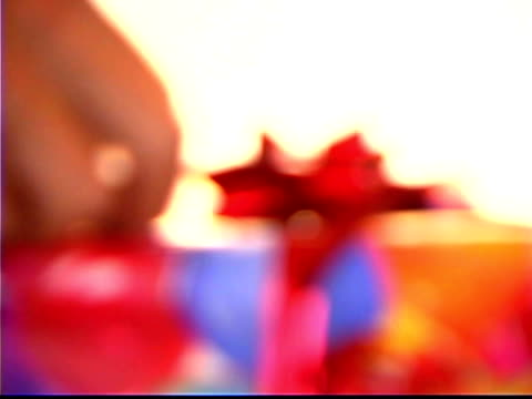 Blurred close-up of hands adjusting a bow on a present.
