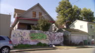 Boarded up house with graffiti laden fence along front of property on residential street Foreclosure Poverty Poor