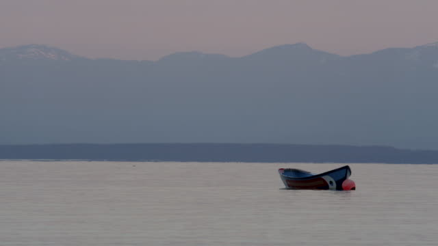 MS Boat attached to buoy floats in the Strait of Georgia with mountains in the distance / Cortes, British Columbia, Canada