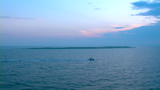 A boat cruises in the Gulf along the Mississippi coastline.