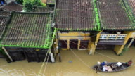A boat cruises over floodwaters surrounding a store in Hoi An, Vietnam.