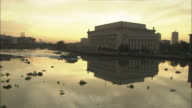 A boat glides past a large government building at golden hour.