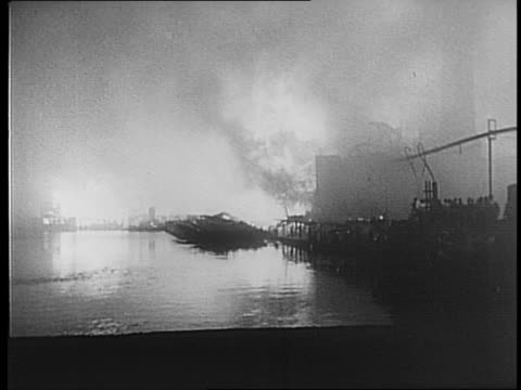 Boat in flames on water / crowd stands back near railroad tracks / firefighters use hoses to shoot water at flaming buildings / shots of warehouses...