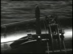 Boat moonlight silhouette moving left VS Crew members rolling short torpedoes off rack TRACKING Torpedoes just below surface WS Explosion at ship [VO...