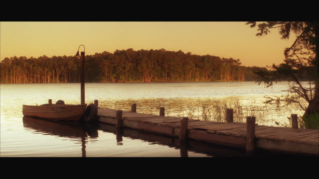 WS Boat moored at wooden pier on lake at sunset