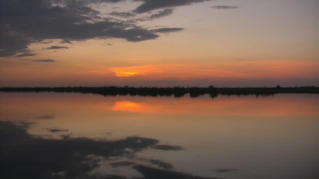 POV, Boat moving on river at sunset, Botswana