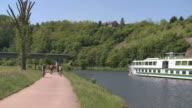 WS Boat moving on river Saar with bikers biking  / Saarburg, Saar-Valley, Rhineland-Palatinate, Germany
