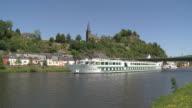 WS PAN Boat moving on river Saar with old town and castle ruin / Saarburg, Saar-Valley, Rhineland-Palatinate, Germany