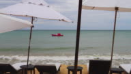 WS Boat on beach with umbrella and sun lounger in foreground / Trancoso, Bahia, Brazil