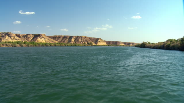 POV Boat on Colorado River with desert shoreline with green vegetation close to water, Blythe, California, USA