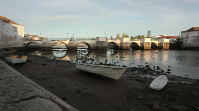 WS Boat on rocky riverbank with medieval bridge on Gilao River in background / Tavira, Algarve, Portugal