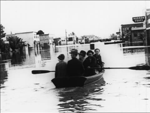 B/W 1926 boat point of view behind people rowing in boat on flooded town street / Sacramento CA / newsreel