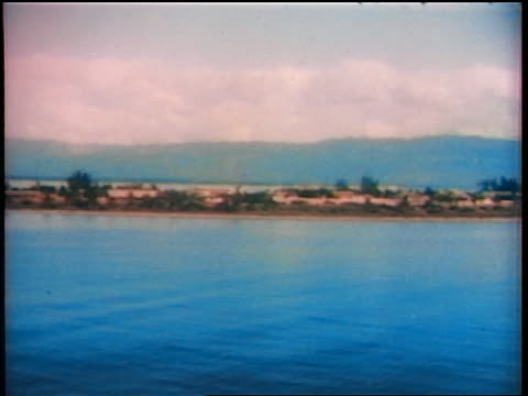 1936 boat point of view buildings + trees on coastline + mountains in background / Port Royal, Jamaica