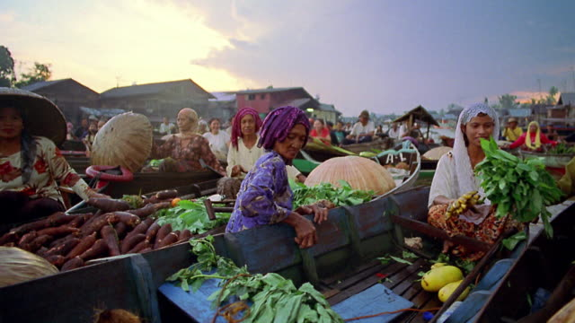 Boat point of view past female vendors exchanging fruit and vegetables at floating market on river / Indonesia