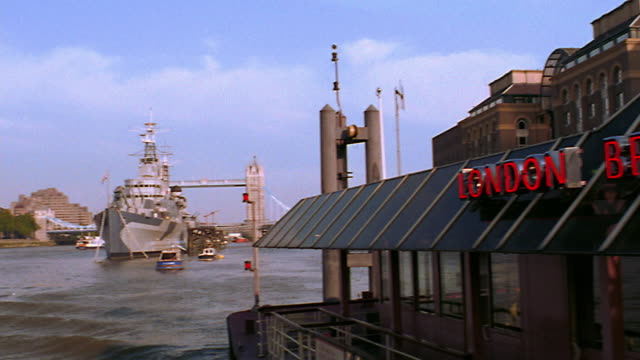 Boat point of view PAN river boat cafe with HMS Belfast + Tower Bridge in background / Thames River, London, England